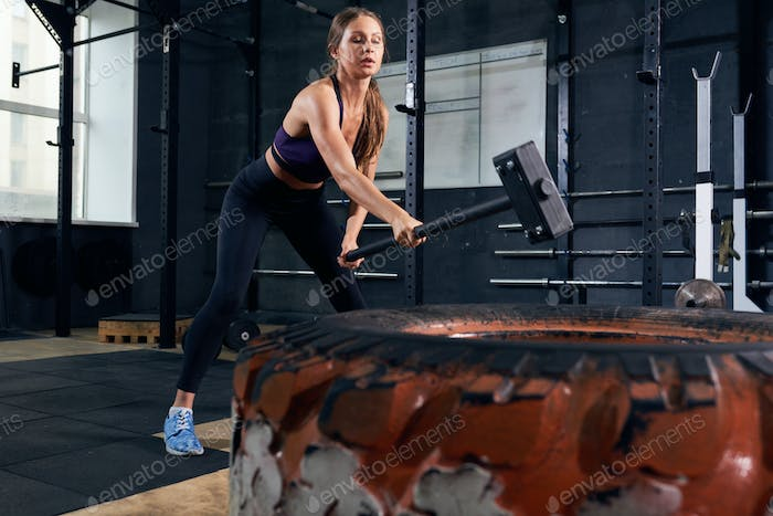 Woman in CrossFit Workout with Hammer