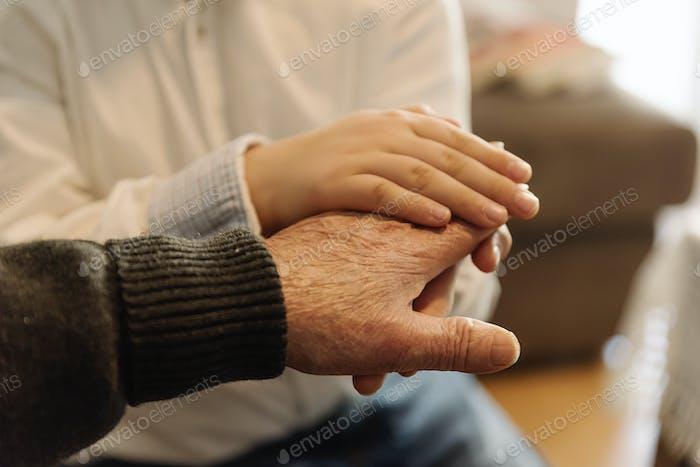 Hand der alten Person, die Hand des Kindes hält.