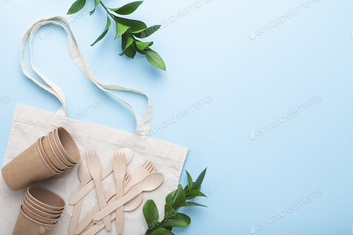 Paper cups, wooden cutlery and cotton bag, free space