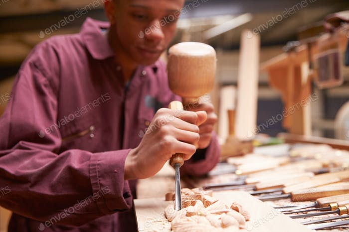 Apprentice Using Chisel To Carve Wood In Workshop