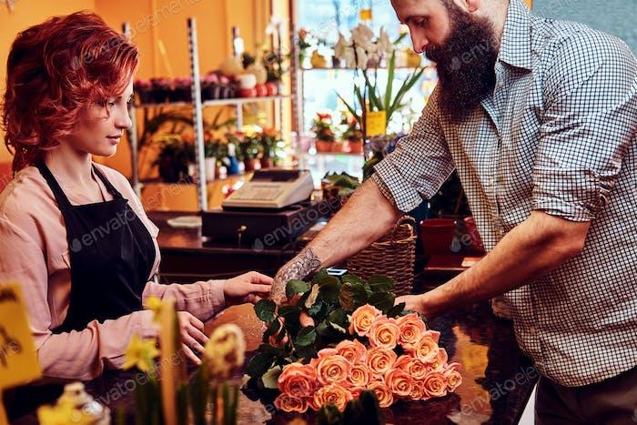 Bärtiger männlicher Kauf Blumenstrauß im Blumenladen.