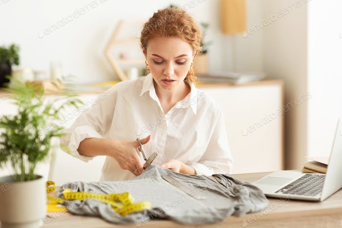 Serious tailor cutting fabric with scissors, sewing costume