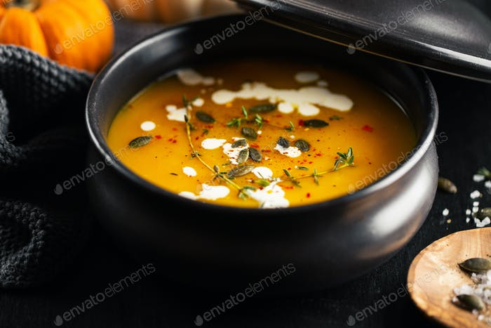 Creamy pumpkin soup served in bowl