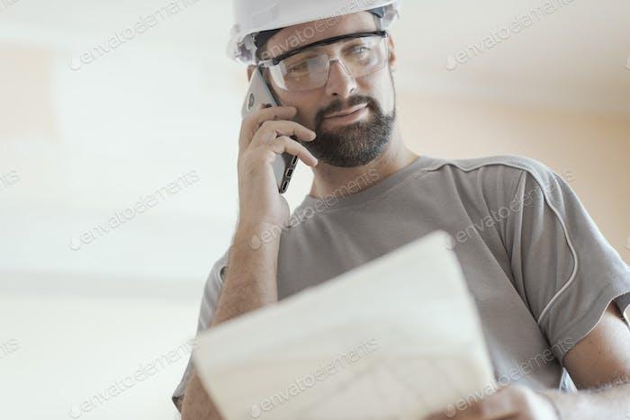 Lächelnder Architekt mit einem Anruf