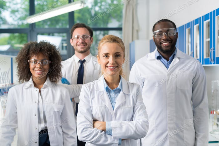 Smiling Group Of Scientists In Modern Laboratory With Female Leader, Mix Race Team Of Scientific