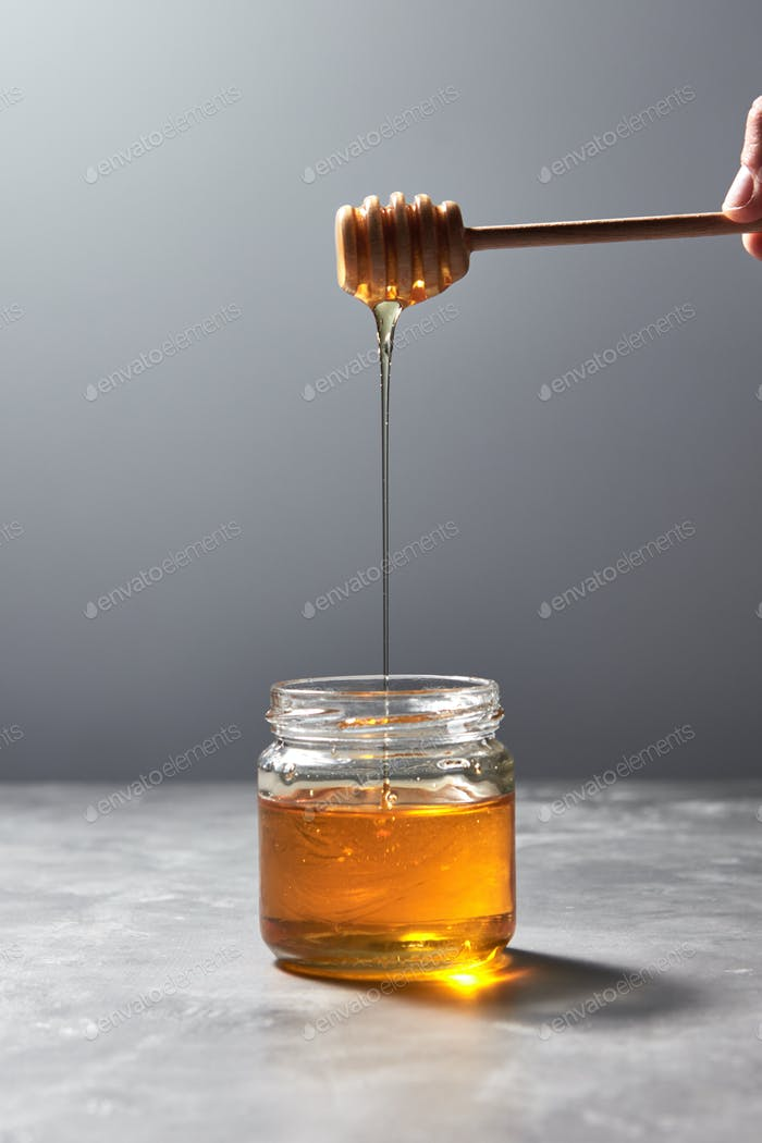 Woman hand hold a wooden stick with dripping sunflower honey in a glass jar on a gray background