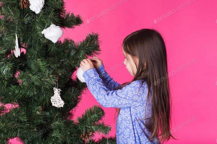 Children, holidays and christmas concept - little girl decorating christmas tree on pink background