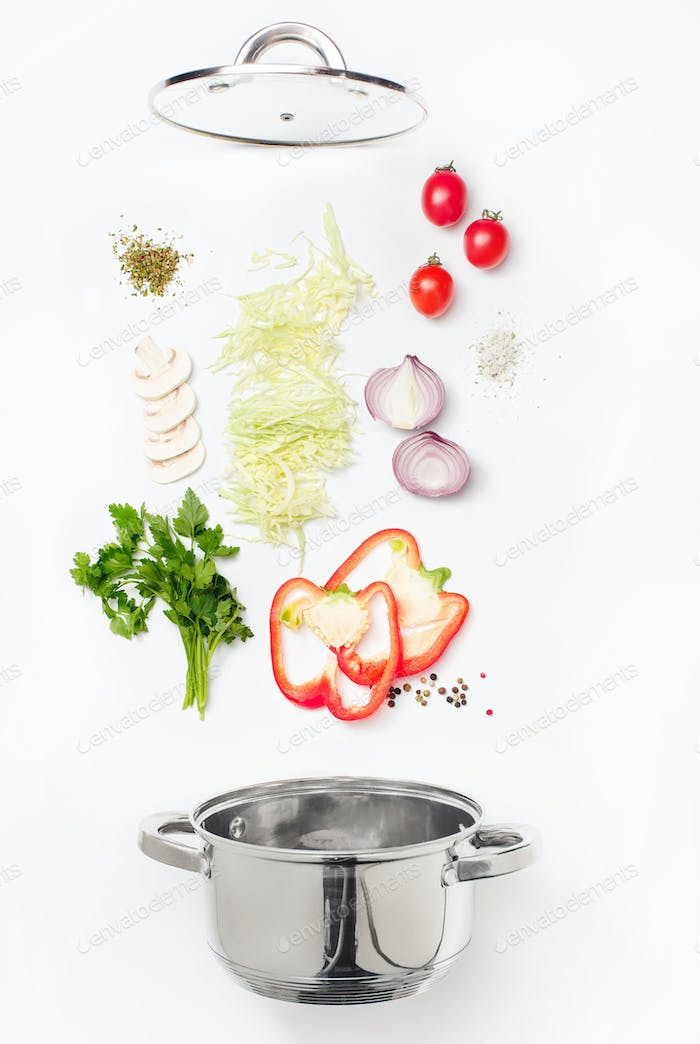 Assorted fresh vegetables falling into a bowl, on white background