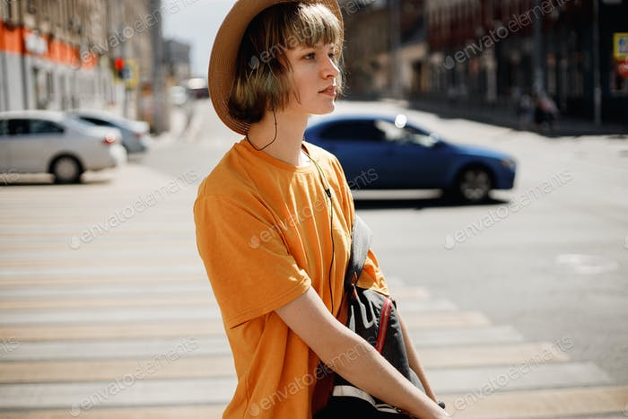 Young girl in a yellow t-shirt and straw hat walks with a backpack along a city street on a summer
