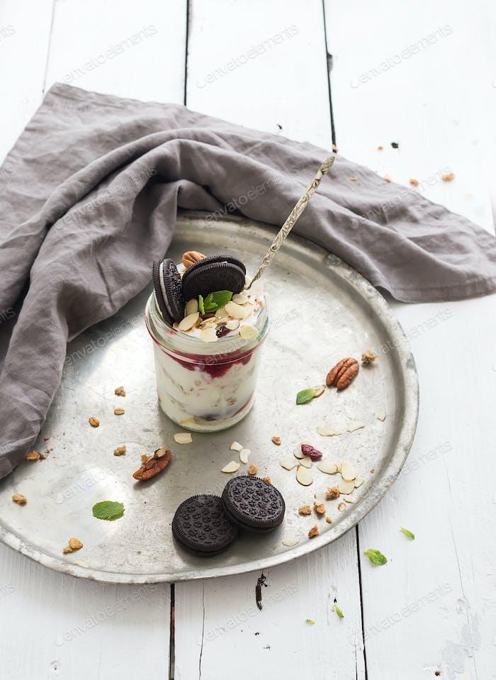 Yogurt oat granola with berries, honey, nuts and cookies in glass jar on vintage metal tray