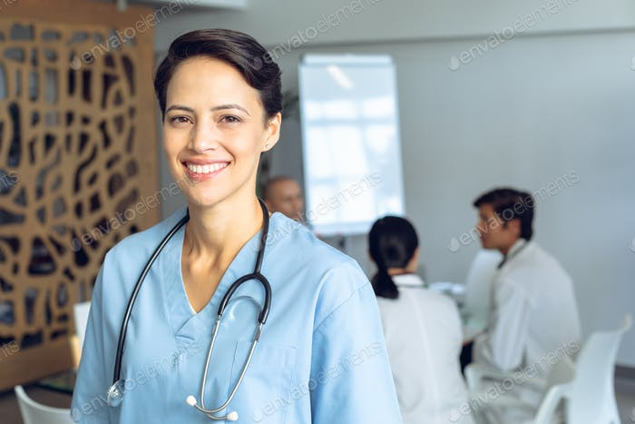 Happy female Caucasian nurse looking at camera in conference room in hospital.