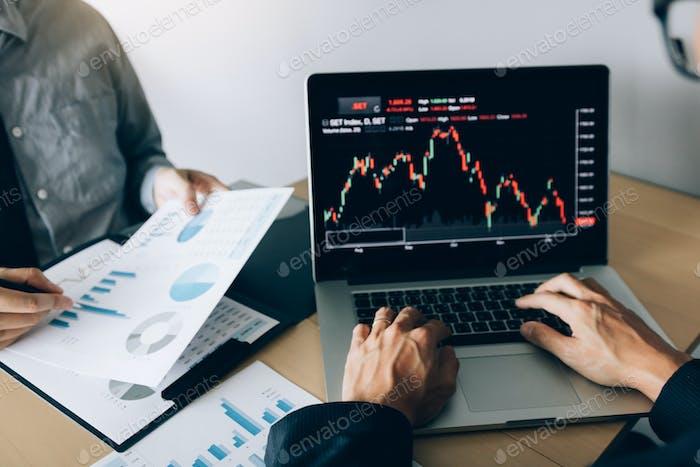los inversores están trabajando juntos para analizar los gráficos de datos de acciones