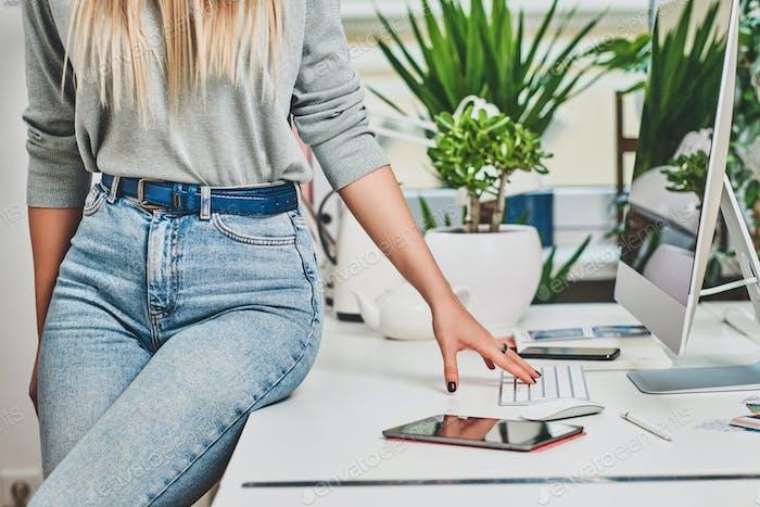Frau in Jeans sitzt auf dem Tisch