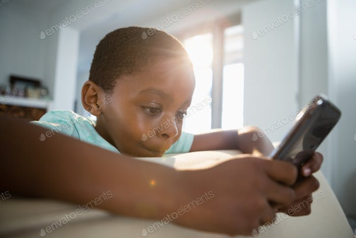 Boy using mobile phone in the living room