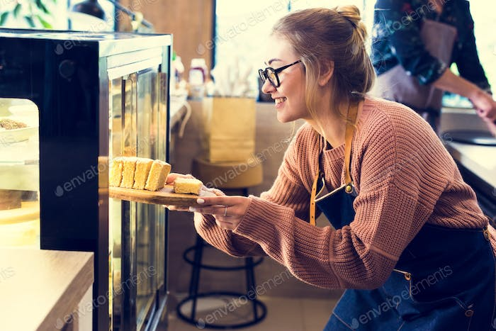 Woman getting cake out of the display fridge
