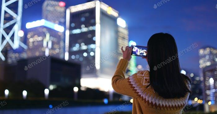 Frau fotografieren auf Handy in der Stadt in der Nacht