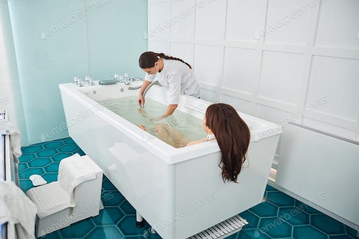 Spa employee concentrating water jet on visitor foot