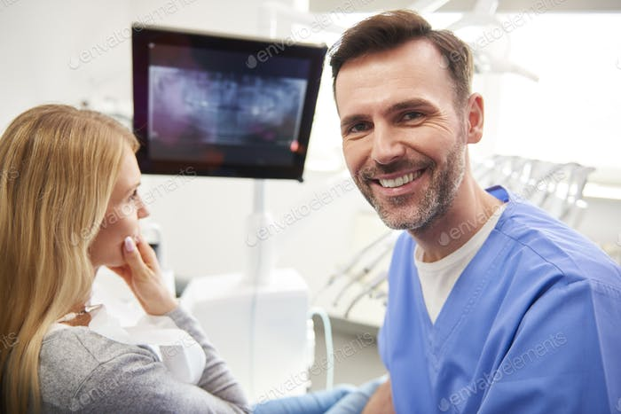Portrait of smiling and confident dentist in dentist's clinic