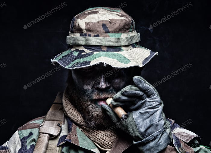 Commando soldier in boonie hat smoking cigar