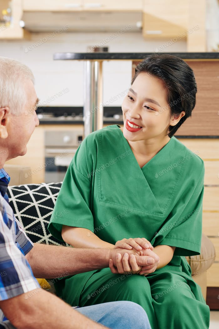 Medical nurse holding hand of senior patient