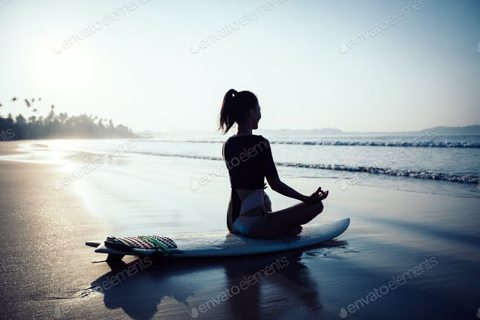 Woman surfer meditation sit on surfboard on beach