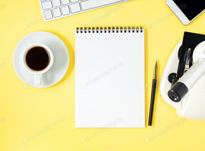 Top view of yellow office desktop with microscope, notepad, computer, smartphone.