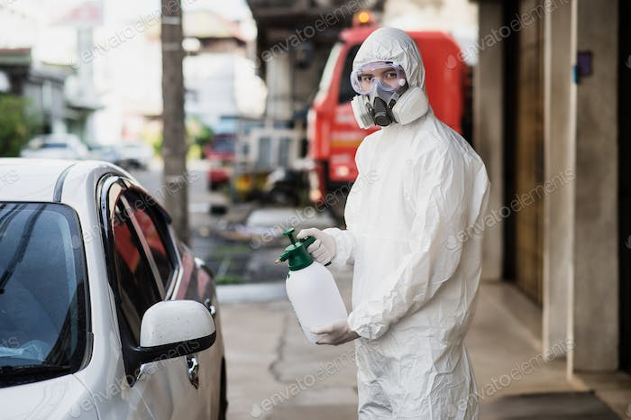 Man in protective suit and mask sprays disinfectant