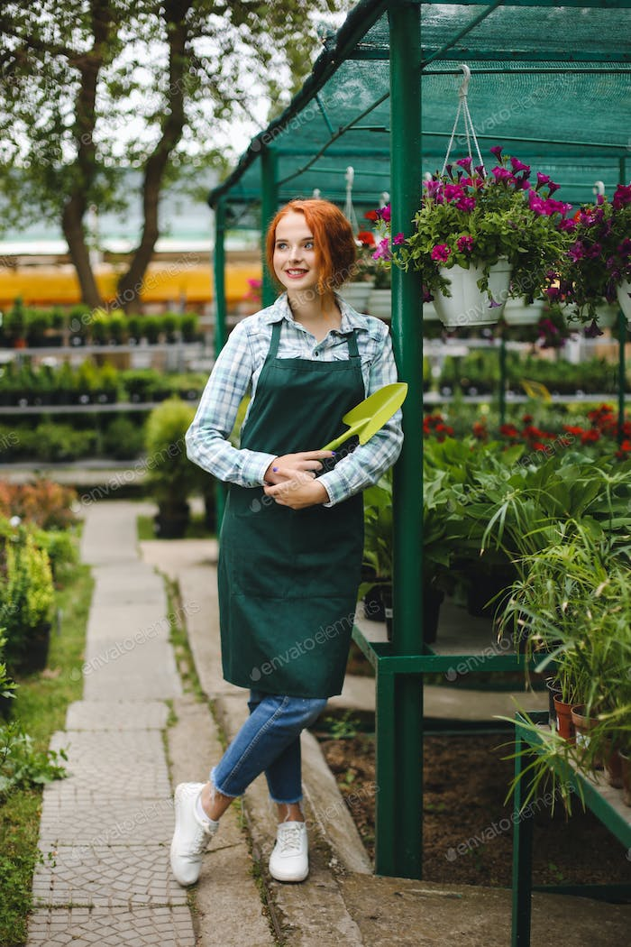 Smiling florist in apron standing with little garden shovel in hand