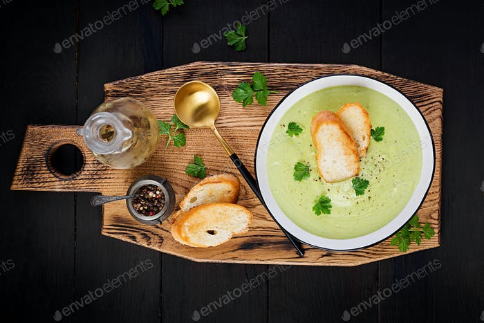 Homemade broccoli cream soup with croutons in white bowl on wooden board