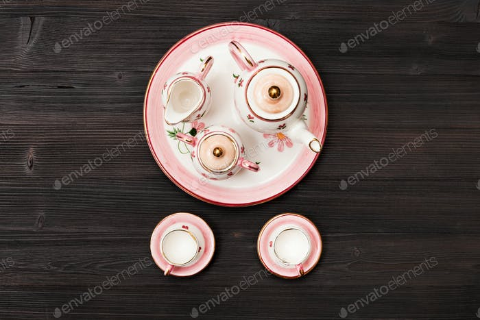 top view of pink tea set on dark brown table