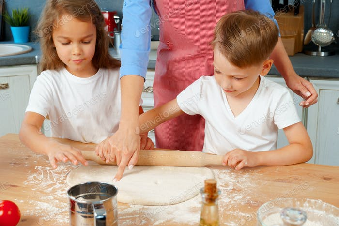 Young blonde woman, mother and her kids having fun while cooking dough