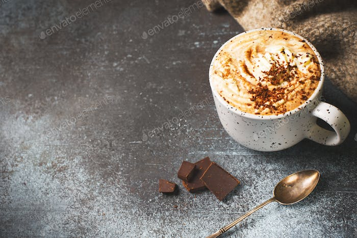 Hot chocolate or cup of coffe with foam and with a piece of chocolate on dark background