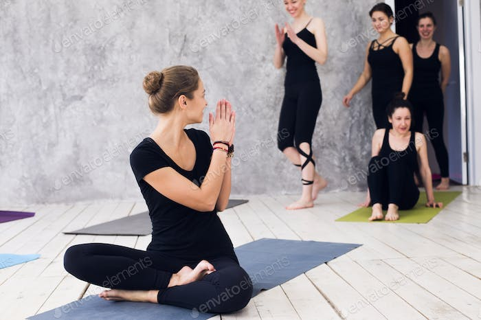 group doing yoga at the gym. Welcoming on yoga class. Exercises starts indoors