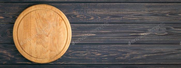 Leere Pizzatafel auf dunklem Holztisch.