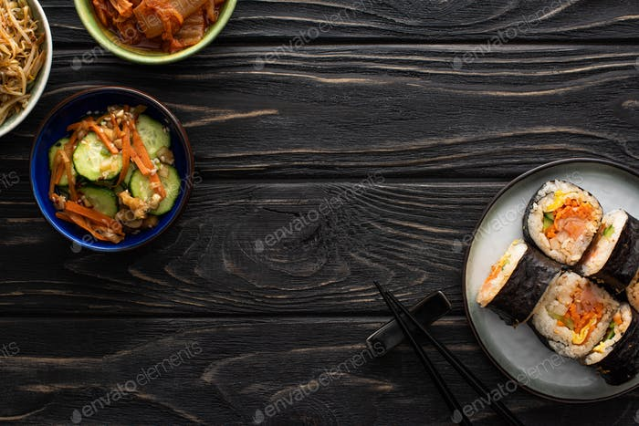 Top View of Plate With Korean Gimbap And Chopsticks Near Tasty Side Dishes on Wooden Surface