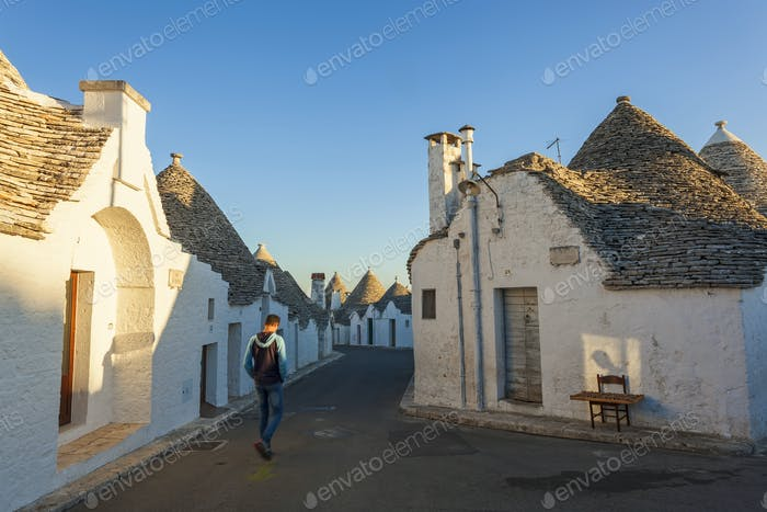 Man walking down Mediterranean street with white washed round stone houses with conical roofs.