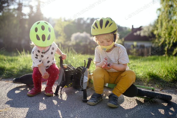 Kleine Kinder mit Gesichtsmasken spielen im Freien mit Fahrrad, Coronavirus Konzept