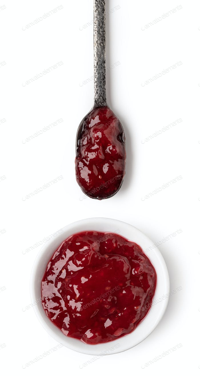 Small glass bowl and spoon of red berry jam