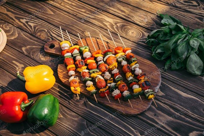 Holzbrett mit Gemüse und Pilzen am Spieß gekocht im Freien auf Grill