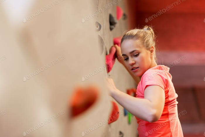 young woman exercising at indoor climbing gym