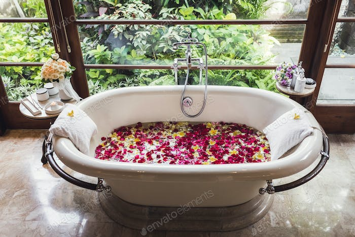 Bath tube with tropical flowers, spa, relaxation, body care, therapy. Top view