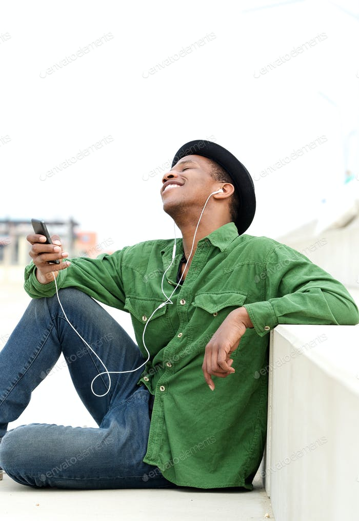 Guy sitting outdoors listening to music