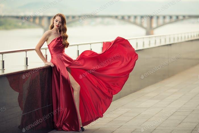 Beautiful Woman In Red Fluttering Dress. Urban Background.