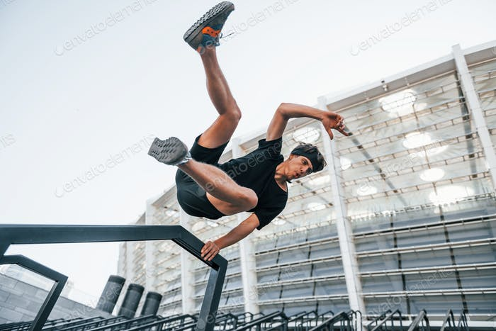 Does parkour. Young man in sportive clothes have workout outdoors at daytime