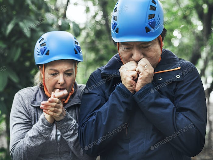 Trekking couple warming their hands