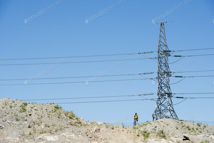 Man standing under electricity pylon