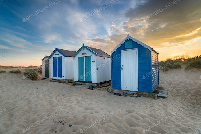 Sunset over a row of pretty beach huts at Southwold