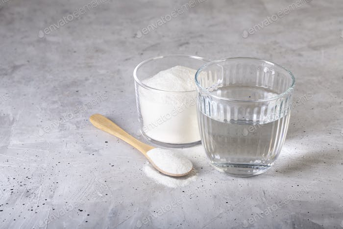 Collagen protein powder - Hydrolyzed. Spoon and glass of water.