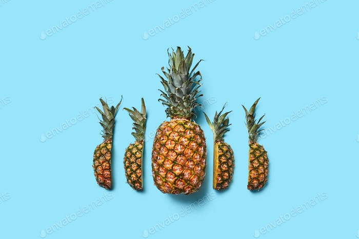 Food composition of ripe pineapple and halved fruit on a blue background with space for text. Flat