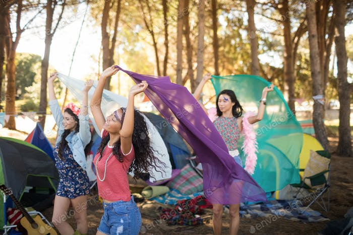 Happy female friends holding scarfs at campsite